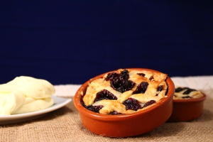 Individual mini blueberry pie served with freshly whipped cream